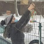 Rūpestingoji mokytoja Rita kelia lesyklėlę į medį.