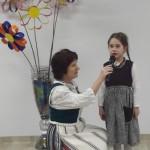Ana Marija deklamuoja eilėraštį apie Lietuvą. Jai padeda auklėtoja Rūta.